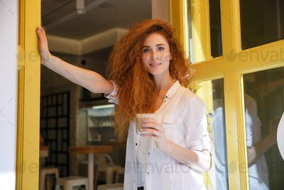 Smiling red hair woman standing and holding cup of coffee