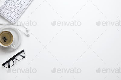 Keyboard With Eyeglasses, Coffee Cup And Earphones On White Desk