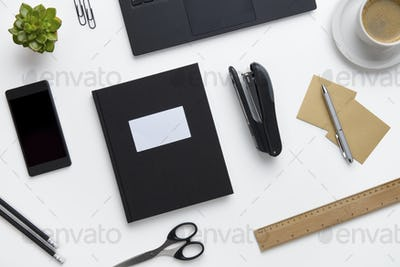 Office Supplies And Devices Arranged On White Desk