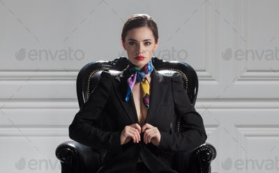 front view of strict business woman in black suit sitting in boss chair