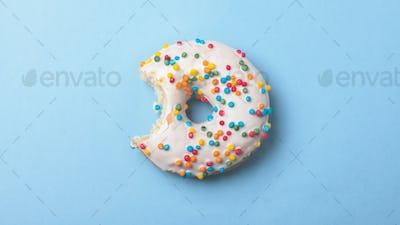 bitten donut on blue surface