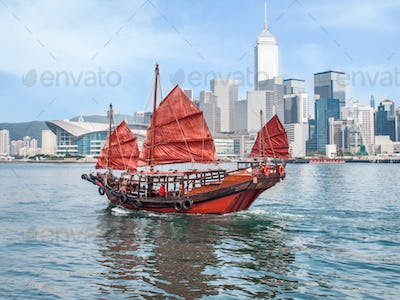 Hong Kong traditional red-sail Junk boat on city skyscrapers background