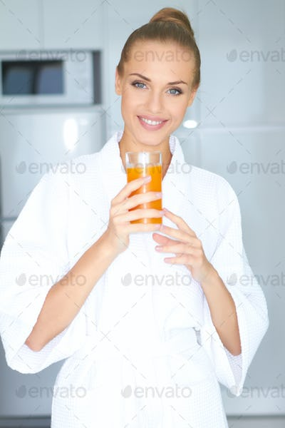 Woman in bath robe drinking orange juice