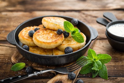 Delicious cottage cheese pancakes or syrniki with fresh blueberry in cast-iron pan