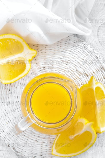 Lemon juice in glass jug and fresh fruits on white wooden background, vitamin drink or cocktail