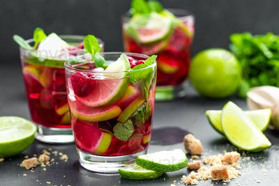 Raspberry mojito cocktail with lime, mint and ice, cold, iced refreshing drink or beverage