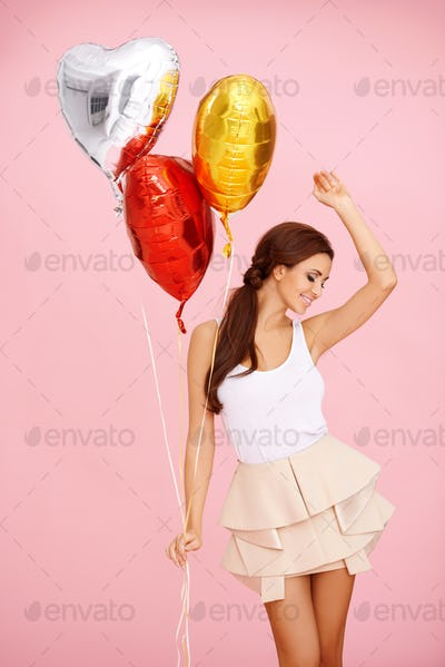 Dancing brunette with balloons