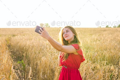 woman taking selfie by smartphone on cereal field