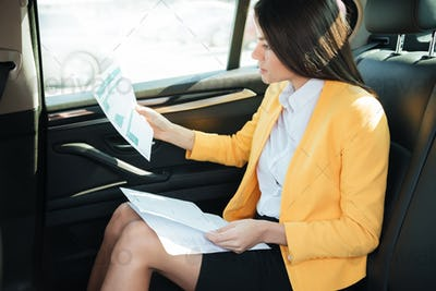 Side view of a concentrated businesss woman analyzing documents