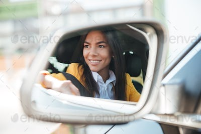 Smiling business woman in side view car mirror