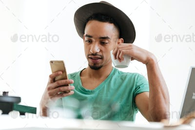 African man in t-shirt using smartphone