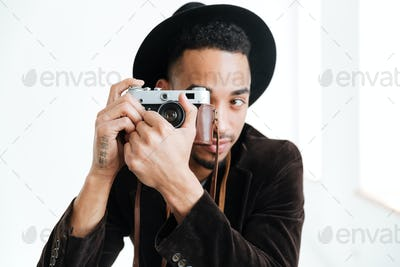 African man making photo on retro camera