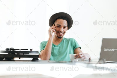 Smiling African man talking on smartphone