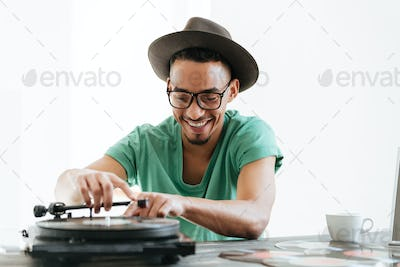 Smiling African man in t-shirt using record-player