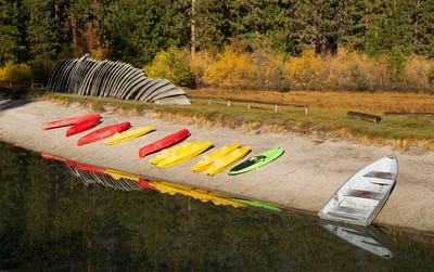 Stacks of Rental Boats Canoes Wait on the Beach
