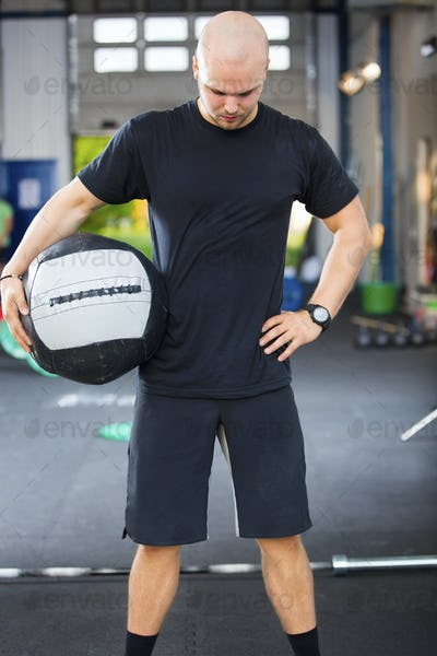 Strong Male Athlete Holding Medicine Ball In Health Club