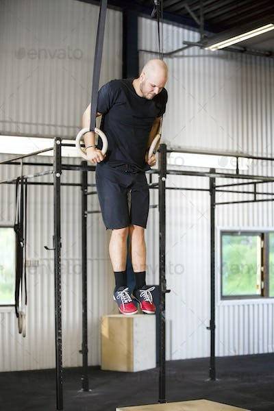 Determined Male Athlete Using Gymnastics Rings In Health Club