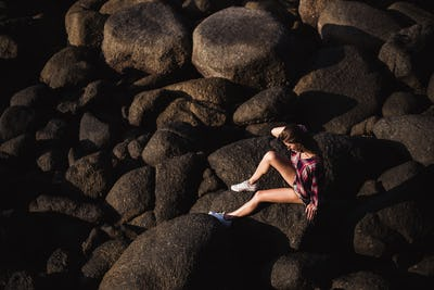 Sexy woman in jeans overall and pink t-shirt sit on big stone at rock beach sea ocean shore. Modern