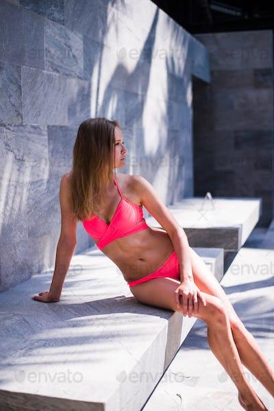 woman sit on concrete near swimming pool at resort