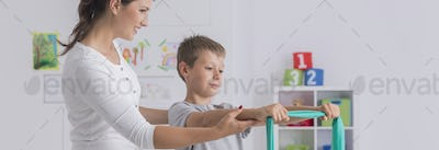 Therapist showing young boy exercises