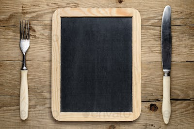 Blank blackboard, fork and knife on old wooden table