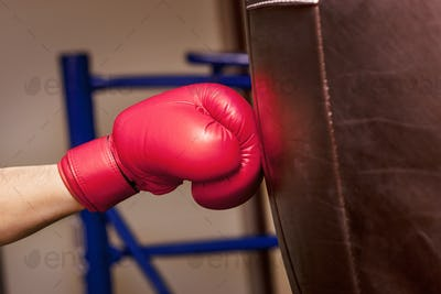 Close-up hand of boxer at the moment of impact on punching bag