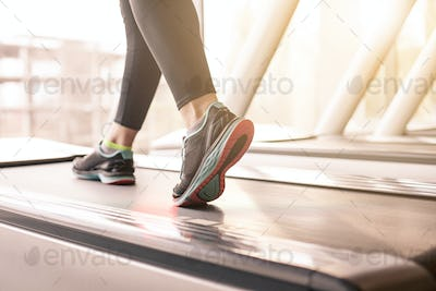 Woman running in a gym on a treadmill concept for exercising, fitness and healthy lifestyle