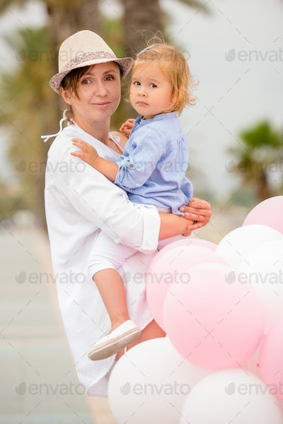 Trendy young mother holding her young daughter
