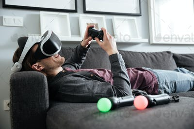 Happy man sitting at home play games with 3d glasses.