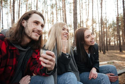 Smiling group of friends sitting outdoors in the forest