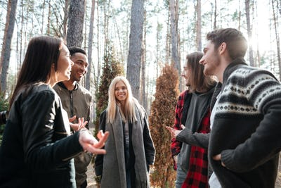 Happy group of friends standing outdoors in the forest