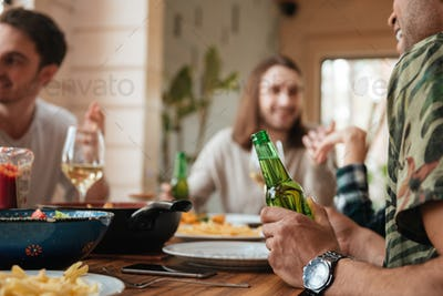 Group of men talking and drinking beer at the table