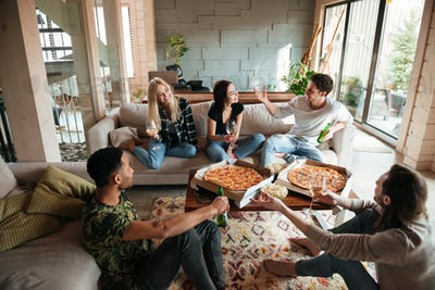 Group of young cheerful friends hanging out together at home