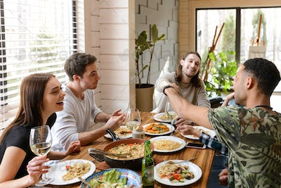 Cheerful young friends eating and having fun at the table