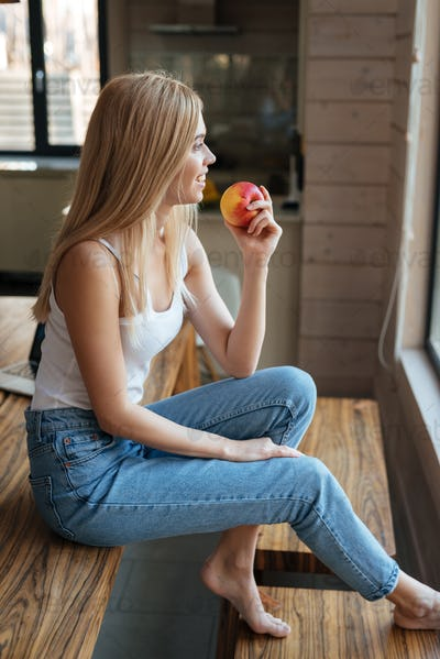 Beautiful young lady sitting at home indoors eating apple