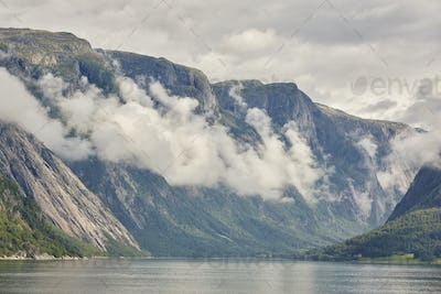 Norwegian fjord landscape with mountains and clouds. Sorfjorden. Norway. Horizontal