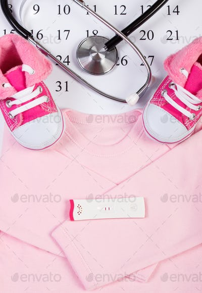 Pregnancy test with positive result, clothing for newborn and stethoscope on calendar