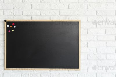 Blackboard hanging on brick wall