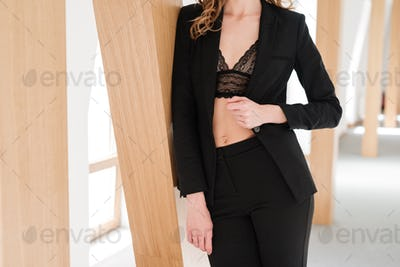 Cropped image of Pretty woman in suit and bra