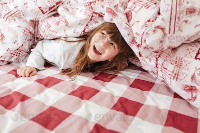 Happy child on bed under blanket