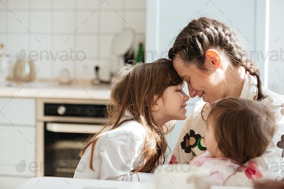 Young woman hugging her daughters
