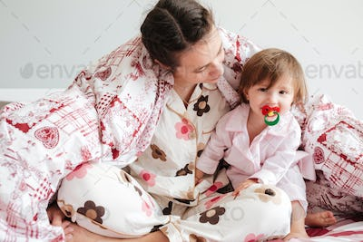 Mother sitting in bed with her daughter