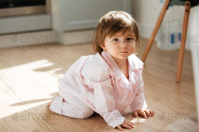 Beautiful little girl in pajamas on wooden floor
