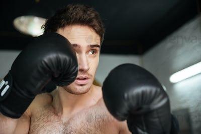 Boxer in gloves preparing to kick