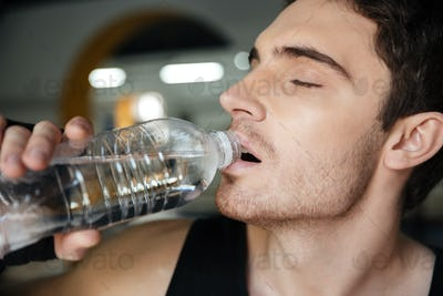 Man sportsman drinking water after training