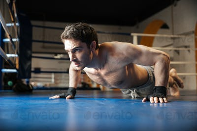 Side view of strong boxer doing push ups
