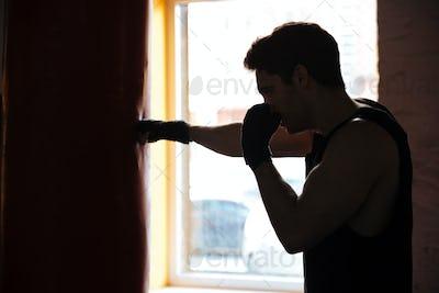Man in shadow kicking the punching bag