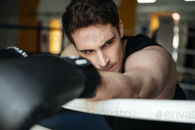Tired sportsman after training leaning on ring