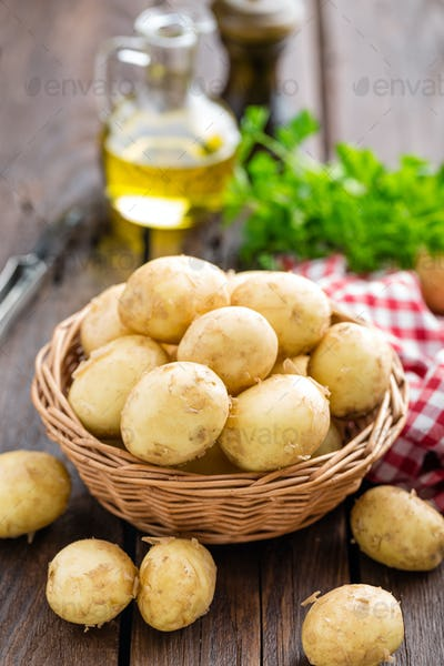 Raw potato in basket on wooden table closeup