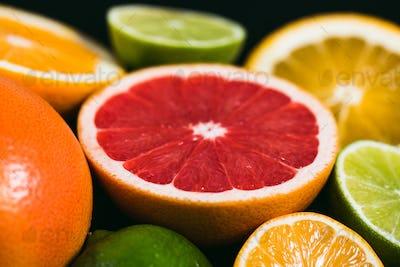 Fresh citrus stihli. Lemons, limes, grapefruit and orange on a black background